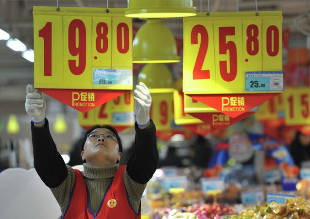 An employee adjusts a price tag at a supermarket in Hefei, January 9, 2015, China.
