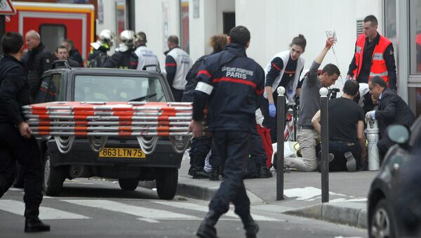 An injured person is treated by nursing staff outside the French satirical newspaper Charlie Hebdo's office, in Paris, Wednesday, Jan. 7, 2015 - Sputnik International