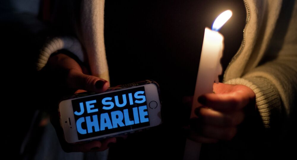A woman holds a cellphone reading 'Je Suis Charlie' (I am Charlie) in support of the victims of the terrorist attack at the French magazine Charlie Hebdo, on January 8, 2015 in front of the French embassy in Mexico City.