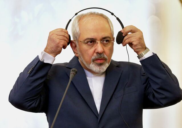 Iranian Foreign Minister Mohammad Javad Zarif listens to translation of a question in a joint press conference with his Turkish counterpart Mevlut Cavusoglu in Tehran, Iran, Wednesday, Dec. 17, 2014.