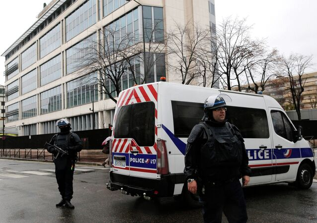 Heavily armed police officers guard the General Directorate for Internal Security headquarters, seen in background, in Levallois Perret, outside Paris, Thursday, Jan. 8, 2015