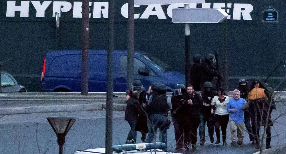Security officers escort released hostages after they stormed a kosher market to end a hostage situation