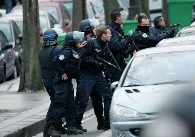 Police stand with their weapons drawn as they surround a bank during an attempted robbery in Paris, near Porte de Saint-Mande, on January 9, 2015