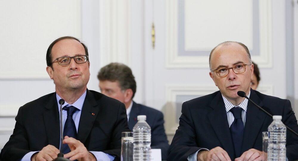French President Francois Hollande (L) holds a crisis meeting with Interior Minister Bernard Cazeneuve (R) and French prefects at the Interior Ministry in Paris