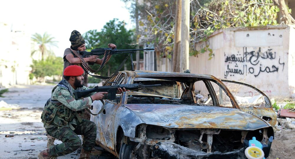 Pro-government Libyan forces, who are backed by locals, aim their weapons during clashes in the streets with the Shura Council of Libyan Revolutionaries, an alliance of former anti-Gaddafi rebels, who have joined forces with the Islamist group Ansar al-Sharia, in Benghazi
