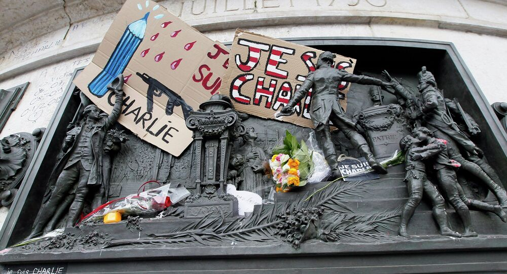 A placard with a news cartoon by French cartoonist Plantu is seen placed amongst other tributes on the statues at the Place de la Republique in Paris