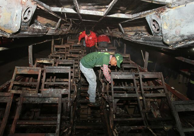 Pakistani rescue workers search through the wreckage of a passenger bus destroyed after colliding with an oil tanker on a highway near Karachi, Pakistan, early Sunday, Jan. 11, 2015.