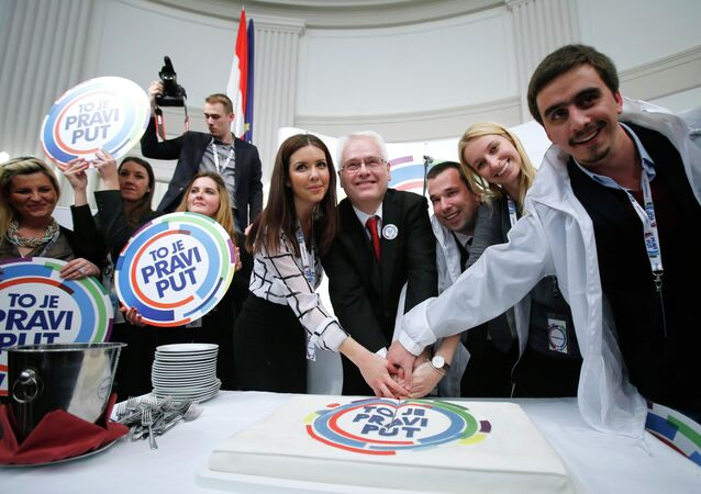 Croatian president and presidential candidate Ivo Josipovic (C) cuts a cake with his supporters after the unofficial results in the headquarters in Zagreb