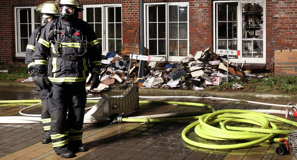 Firefighters stand outside the building of the 'Hamburger Morgenpost' in Hamburg, northern Germany, Sunday morning, Jan. 11, 2015.