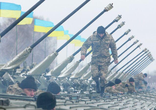 A Ukrainian serviceman walks on armoured personnel carriers (APC)