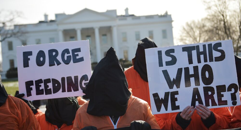 Hooded protestors, some holding placards, take part in a demonstration against the Guantanamo Bay detention facility utside of the White House in Washington