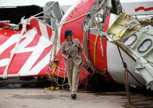 An Airbus investigator walks near part of the tail of the AirAsia QZ8501 passenger plane in Kumai Port, near Pangkalan Bun, Central Kalimantan January 12, 2015.