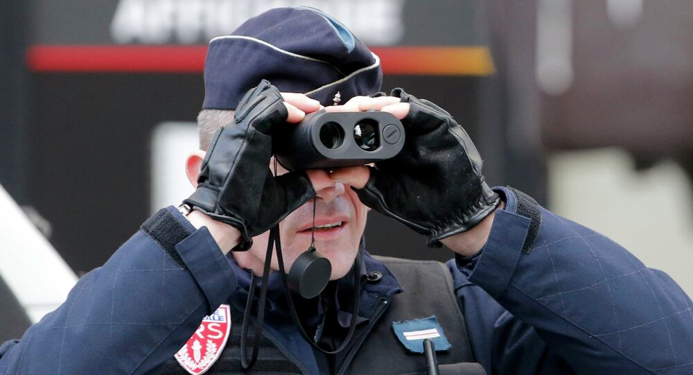 A policeman uses binoculars as he secures the hundreds of thousands of French citizens solidarity march
