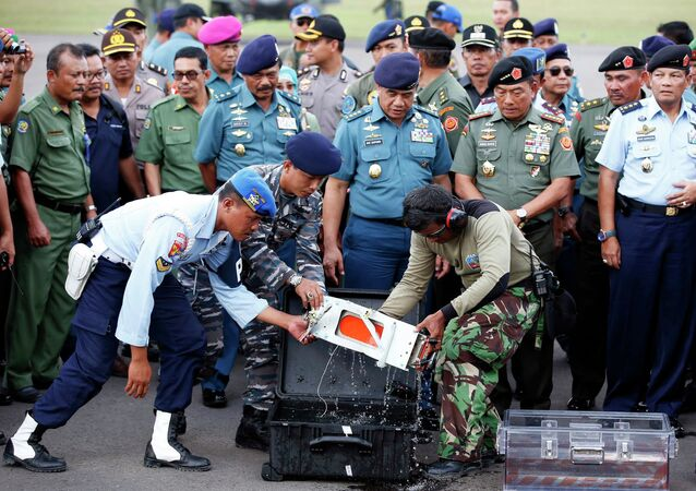 The flight data recorder of AirAsia QZ8501 is transferred to another container at the airbase in Pangkalan Bun, Central Kalimantan January 12, 2015.