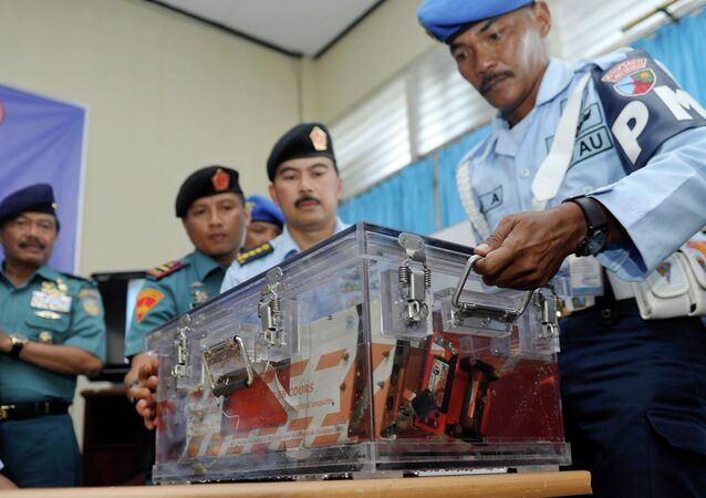 Indonesian military policemen carry the flight data recorder from AirAsia QZ8501 into a media briefing at the airbase in Pangkalan Bun, Central Kalimantan