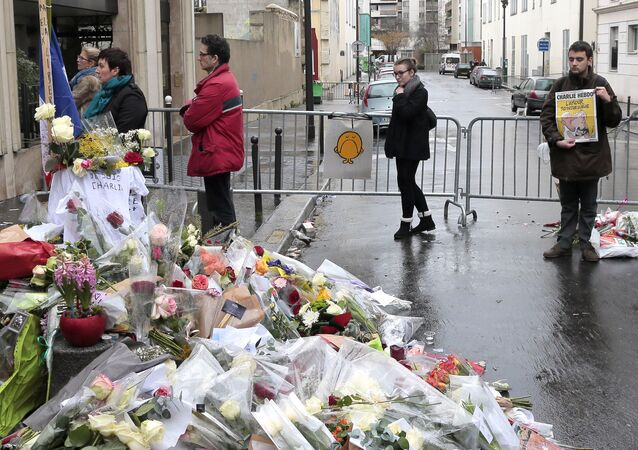 People gather to pay tribute to the satirical newspaper Charlie Hebdo in front of the weekly's office