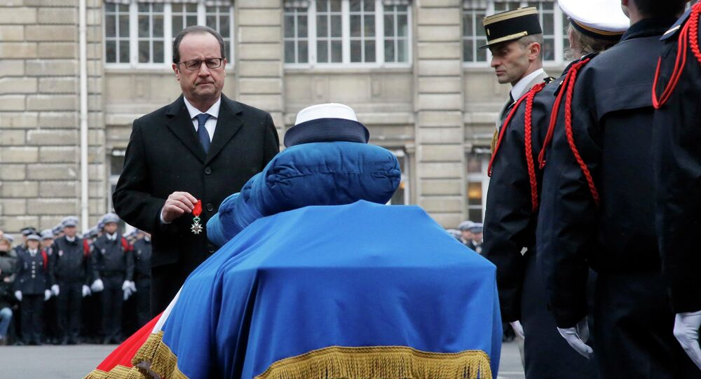 French President Francois Hollande holds a medal in front of the coffin of late police officer Clarissa Jean-Philippe during a national tribute at the Paris Prefecture for the three police officers killed during last week's attacks by Islamic militants, January 13, 2015.