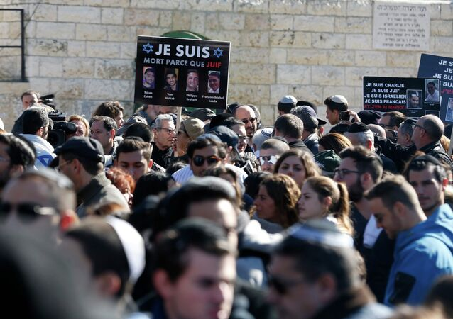 A mourner holds a placard with pictures of the victims of an attack on a Paris grocery on Friday, during their joint funeral in Jerusalem January 13, 2015.