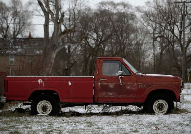 An older Ford F-250 pick-up truck with rust spots sits in the yard of a home in Detroit, Michigan January 8, 2015