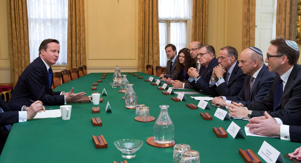 British Prime Minister David Cameron (L) talks with members of the Jewish Leadership Council including Gerald Ronson (4L) and Jonathan Goldstein (R) during their annual meeting at 10 Downing Street in London on Janurary 13, 2015