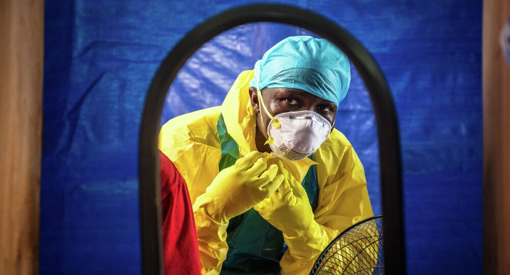 Healthcare worker dons in protective gear before entering an Ebola treatment center in the west of Freetown, Sierra Leone