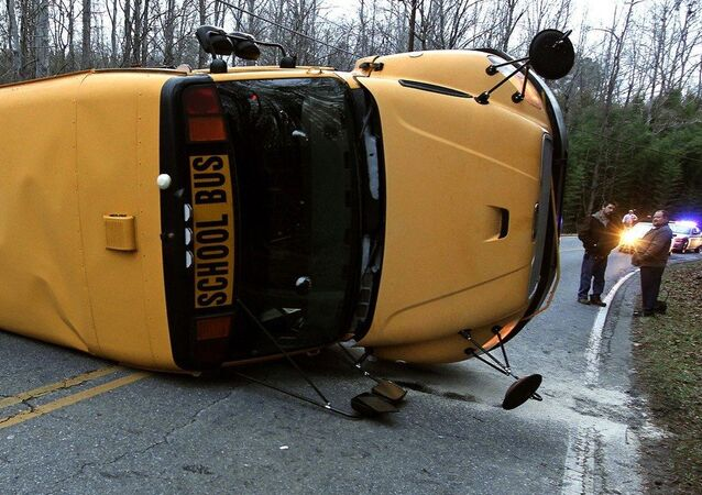 A North Carolina Highway Patrol officer works the scene after a Gaston County school bus overturned in Gastonia, N.C. Wednesday, Jan. 14, 2015