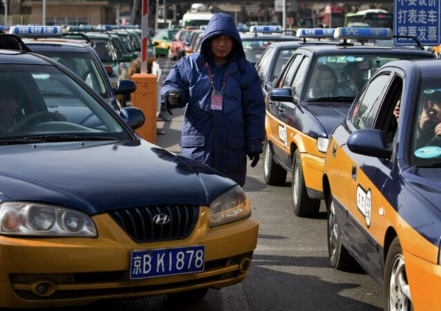 A worker stands between the taxis line waiting for customer in Beijing