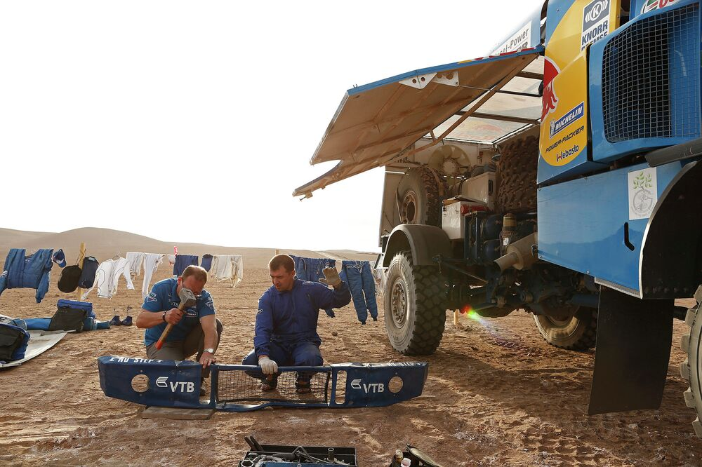 Members of team KAMAZ-master straighten out a bumper during a campout on one of the stages of the Dakar 2015 rally