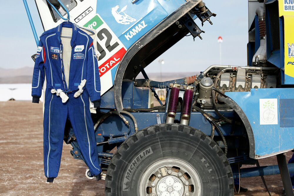 A team KAMAZ-master driver's uniform hangs on the rear-view mirror of one of the trucks during a stop along the Dakar 2015 rally