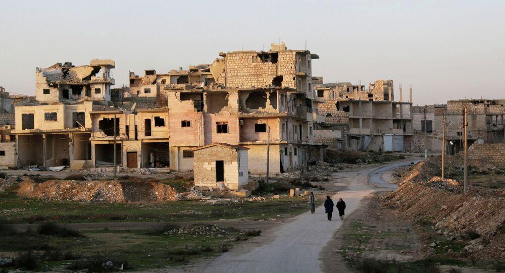 Residents walk near damaged buildings in Maaret al-Naaman town in Idlib province January 14, 2015