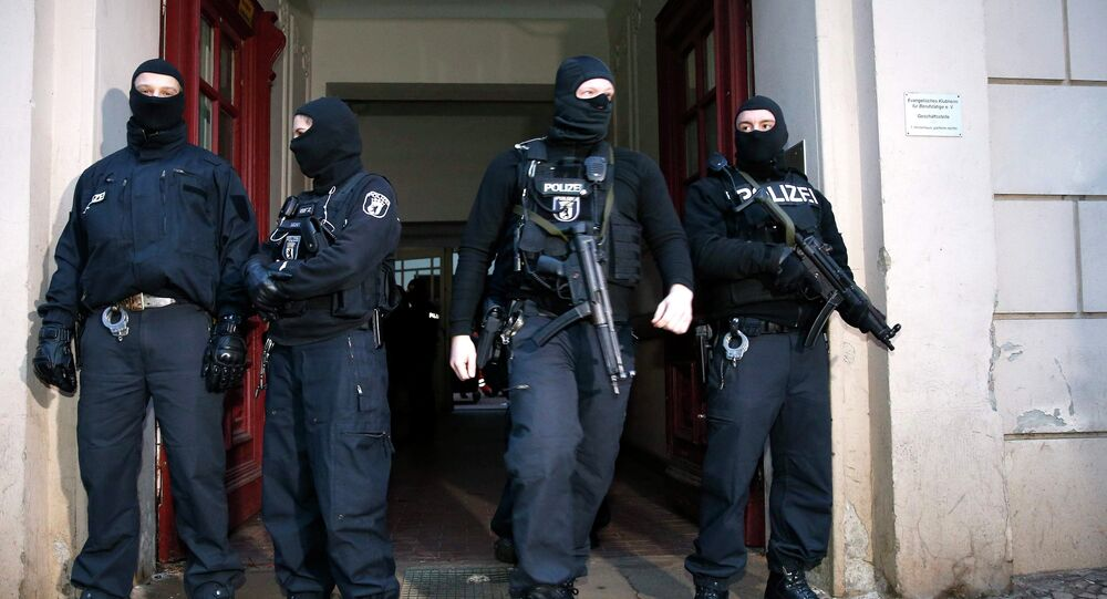 German special police units stand in front of an entrance of an apartment building in the Wedding district in Berlin January 16, 2015