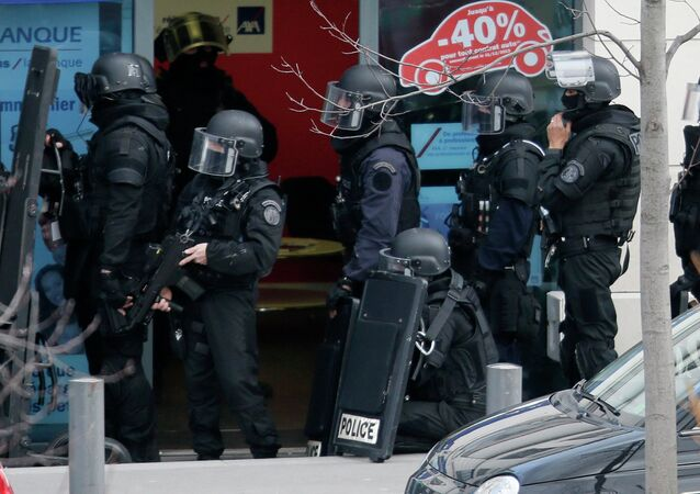 Members of special French RAID forces secure the area next to the post office in Colombes outside Paris, were an armed gunman is holding hostages January 16, 2015