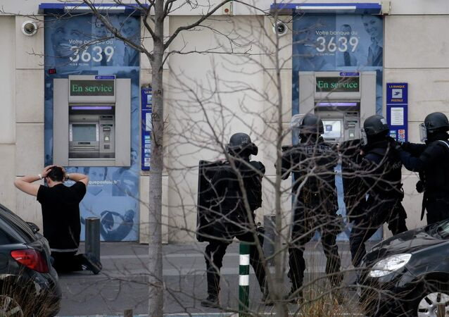 A suspect in a hostage taking situation is detained by members of special French RAID forces outside the post offices in Colombes outside Paris, January 16, 2015