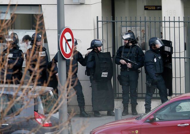 Members of the French police forces secure the area next to the post office in Colombes outside Paris, were an armed gunman is holding hostages January 16, 2015