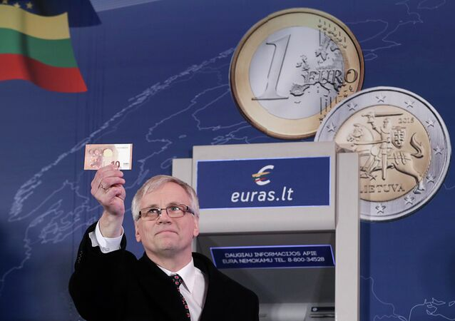 Lithuania's Minister of Finance Rimantas Sadzius holds a euro banknote during an event celebrating Lithuania's joining the euro zone in Vilnius January 1, 2015