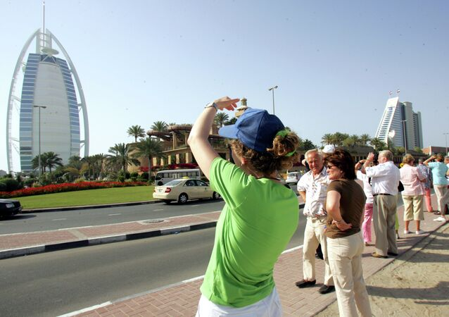 Tourists take pictures of the Burj al-Arab (L) and Jumeirah Beach Hotel in Dubai