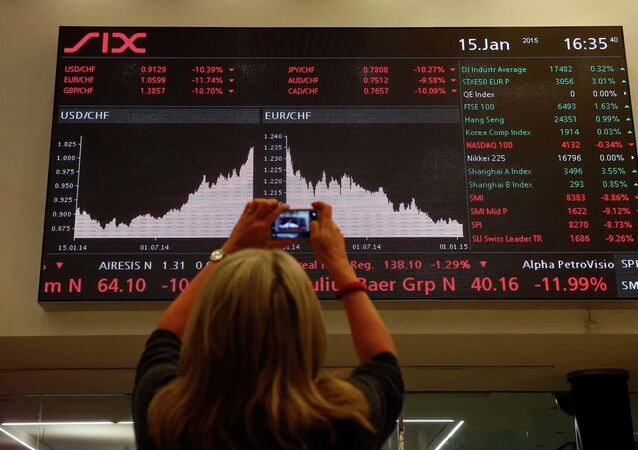 A woman takes a picture of a display showing the Swiss franc's exchange rate against the Euro and other currencies at the Swiss stock exchange in Zurich January 15, 2015