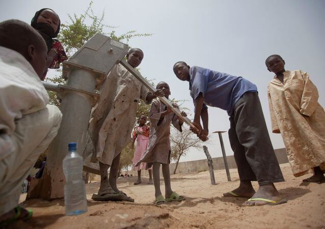 Children pump water to drink from a well in the courtyard of a walk-in feeding center in Dibinindji, a desert village in the Sahel belt of Chad, Wednesday, April 18, 2012