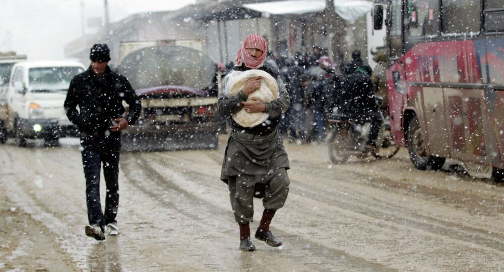 A man carries a bag of bread during a snow storm in Kafranbel town in the Idlib governorate January 15, 2015