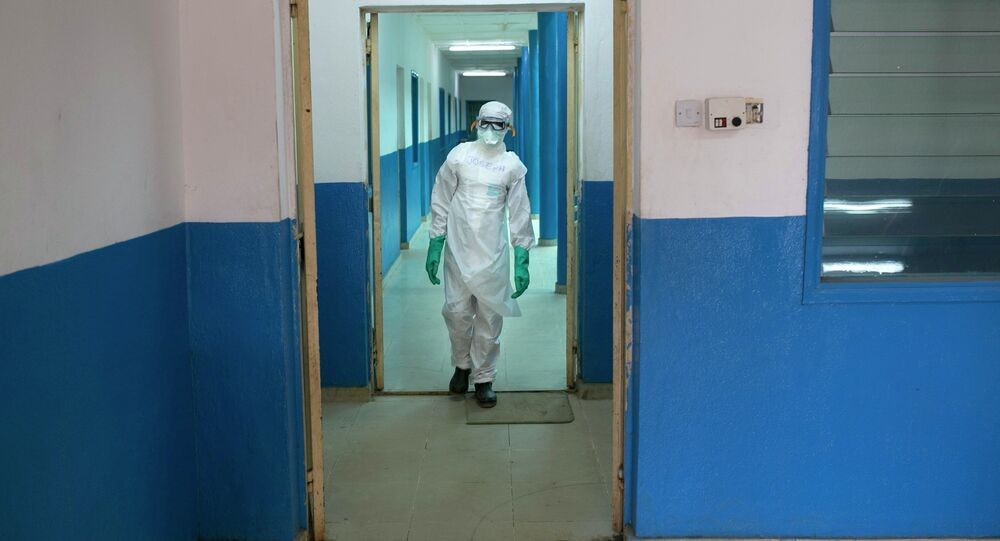A health worker in protective gear walks inside a Red Cross facility in the town of Koidu, Kono district in Eastern Sierra Leone December 19, 2014