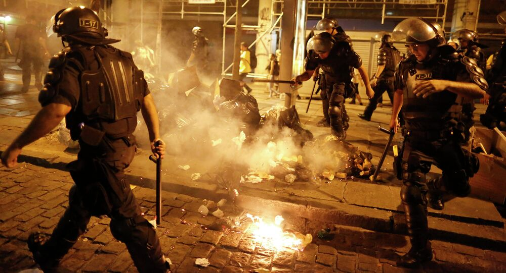 Riot police officers walk past garbage lit on fire by protestors during a demonstration against the increase on bus fares in Rio de Janeiro, Brazil, Friday, Jan. 9, 2015