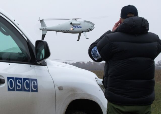 A member of the Organization for Security and Co-operation in Europe (OSCE) mission to Ukraine watches a drone take off during a test flight