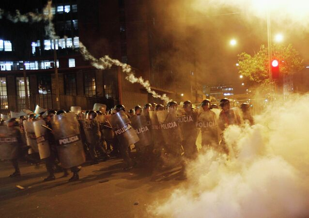 Riot police throw tear gas canisters at protesters during a march against the government's new Youth Labour Law in Lima