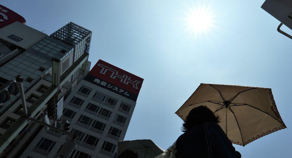 Pedestrians walk under the sun in Tokyo's shopping district Ginza on July 25, 2014