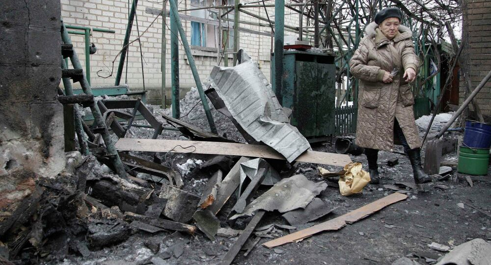 A woman looks at debris in front of a house, which according to locals, was recently damaged by shelling, in Donetsk, eastern Ukraine, January 17, 2015