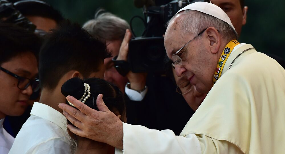Pope Francis (R) reaches out to a child during his visit to the University of Santo Tomas in Manila