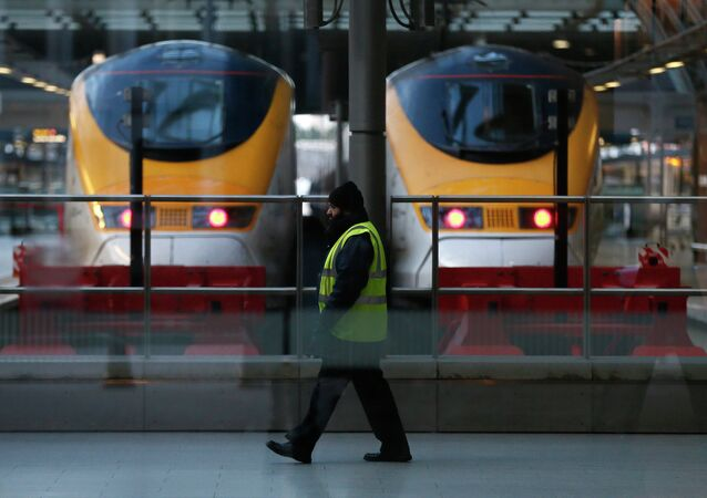 A worker walks past high speed trains at St Pancras International Station in London