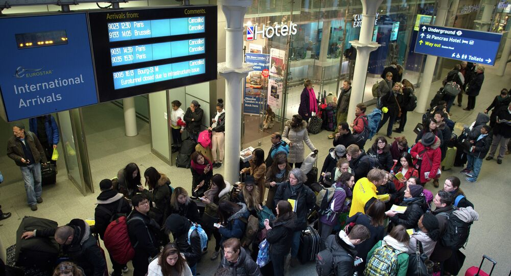 Passengers wait in the long queues at Saint Pancras International station in London