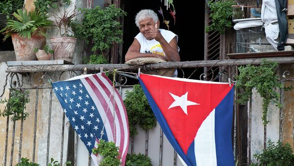 A Cuban gives the thumbs up from his balcony decorated with the US and Cuban flags in Havana - Sputnik International