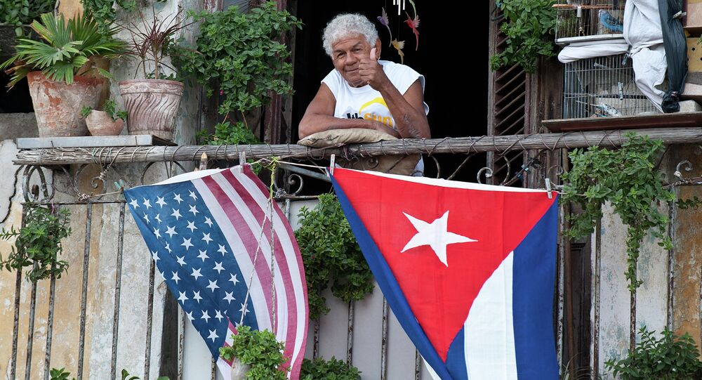 A Cuban gives the thumbs up from his balcony decorated with the US and Cuban flags in Havana